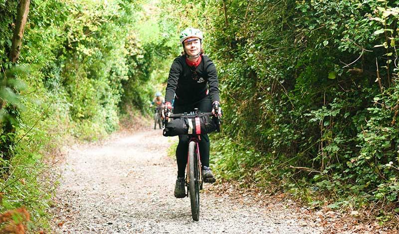 a woman riding a bike through a woodland trail