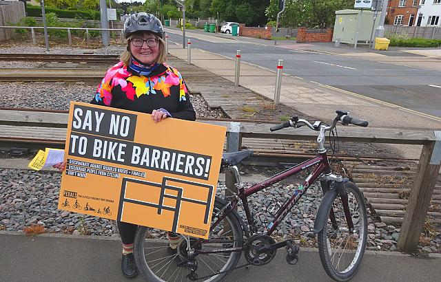 Smiling female cyclist holding a 'No To Bike Barriers' sign at our protest against barriers on cycle paths