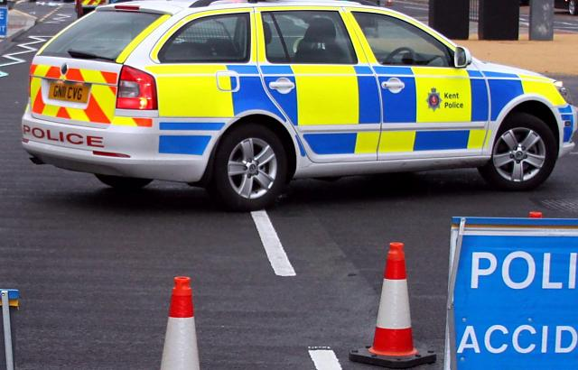 Police car sits on a road behind cones and an accident warning sign