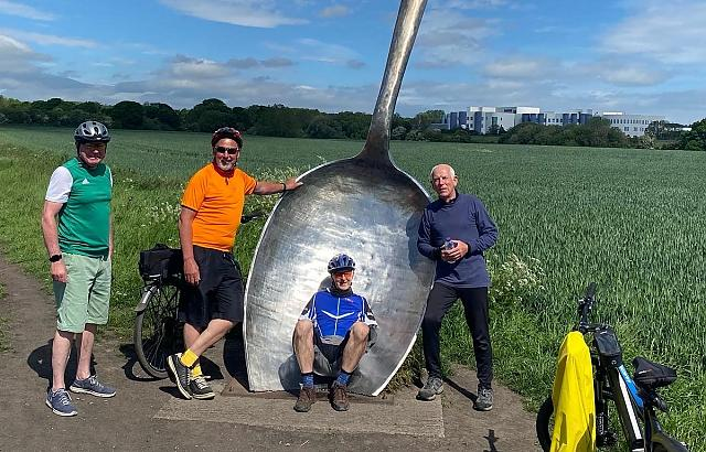 Group ride with giant spoon sculpture