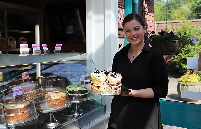 Abbie from the Walled Garden Cafe holds a cake.