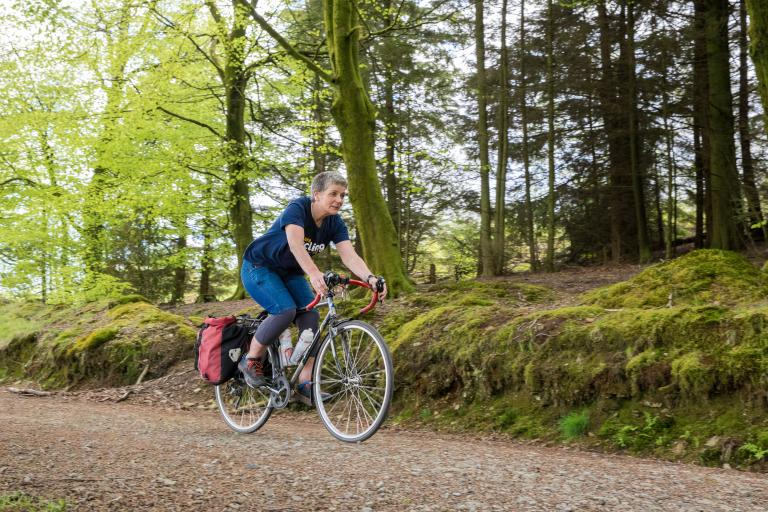 Woman cycling along forest track