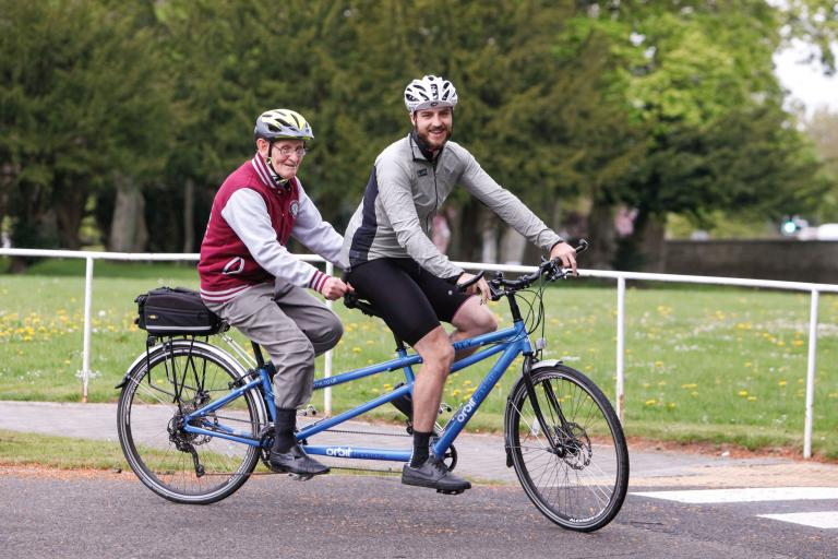 Two men cycling on a tandem