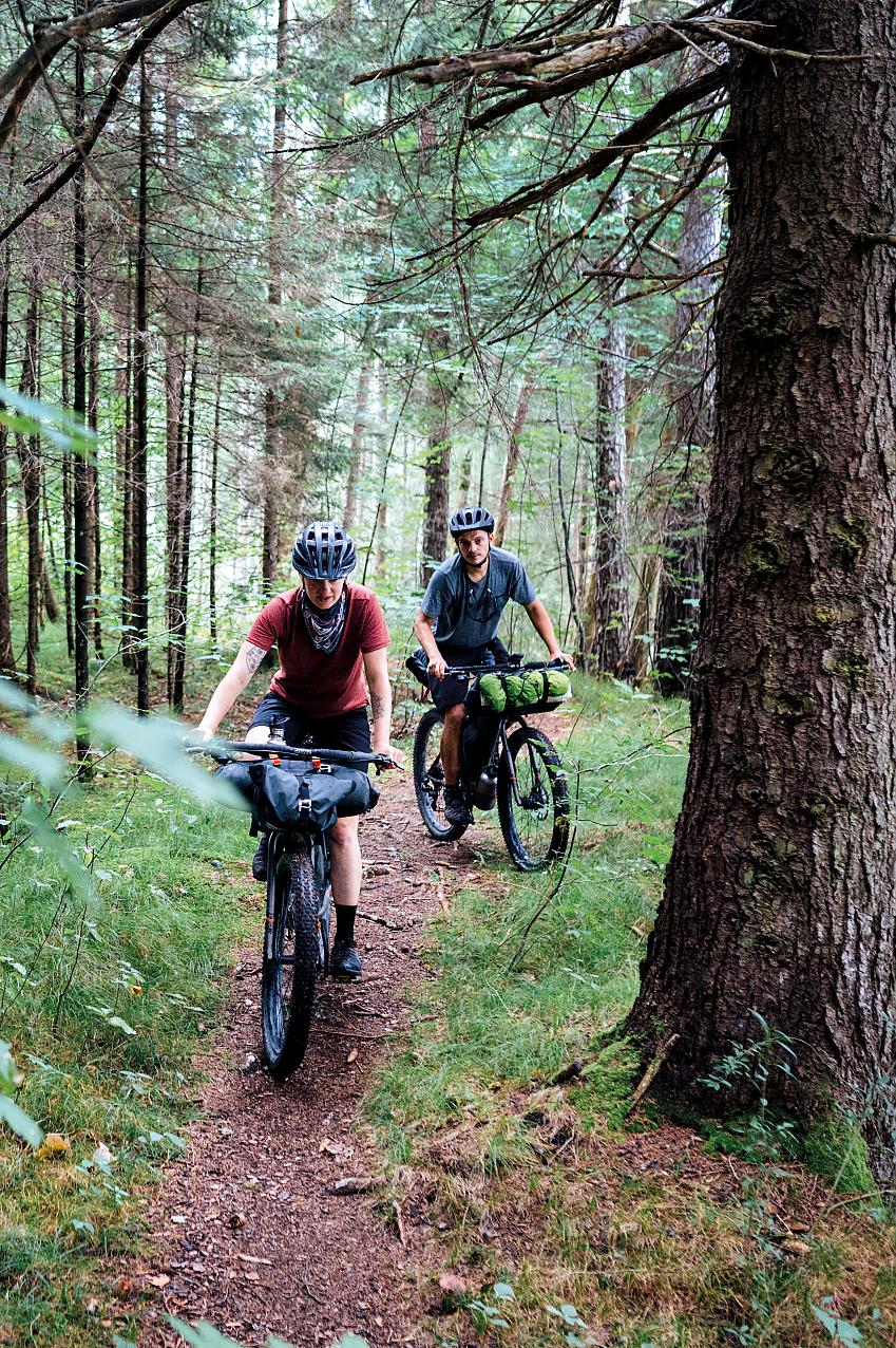 Two cyclists riding with bikepacking bags