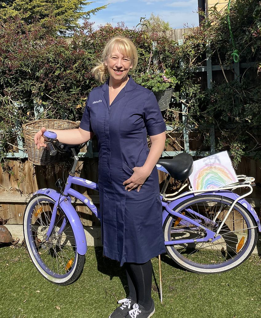 A midwife stands next to her bike