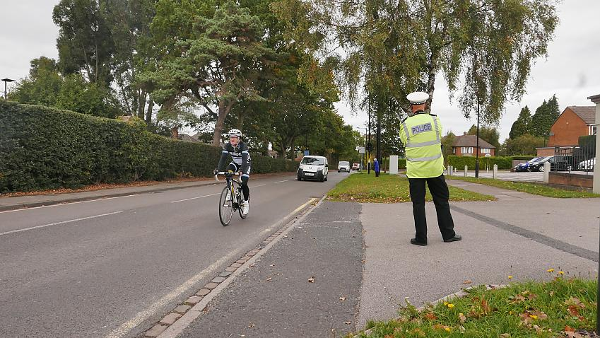 An undercover police officer dressed as a cyclist is observed by a police officer