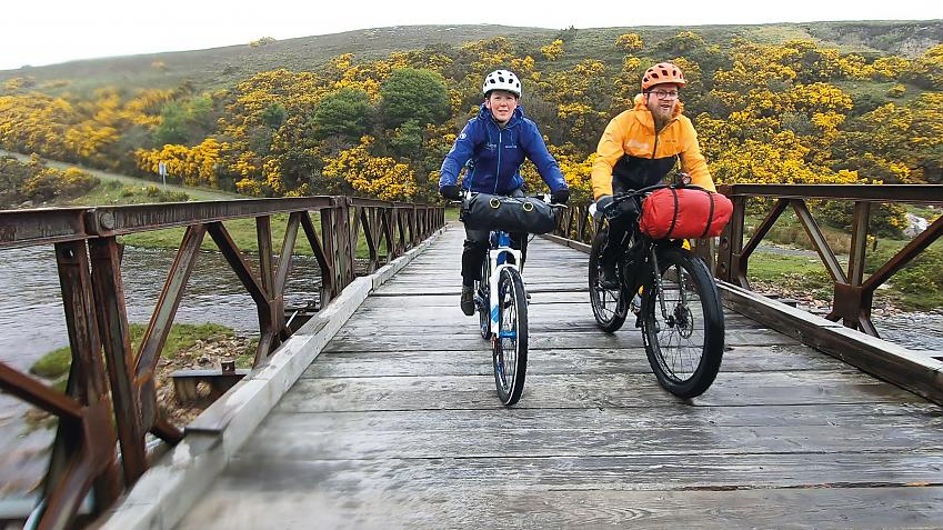 Two riders rumbling over the wooden bridge on the way back from Cape Wrath