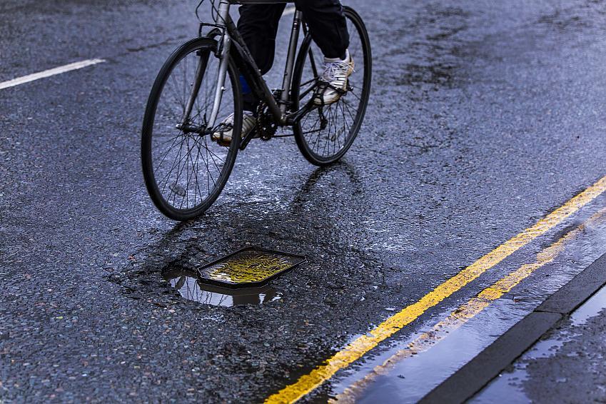 Potholes often form near drains and manhole covers