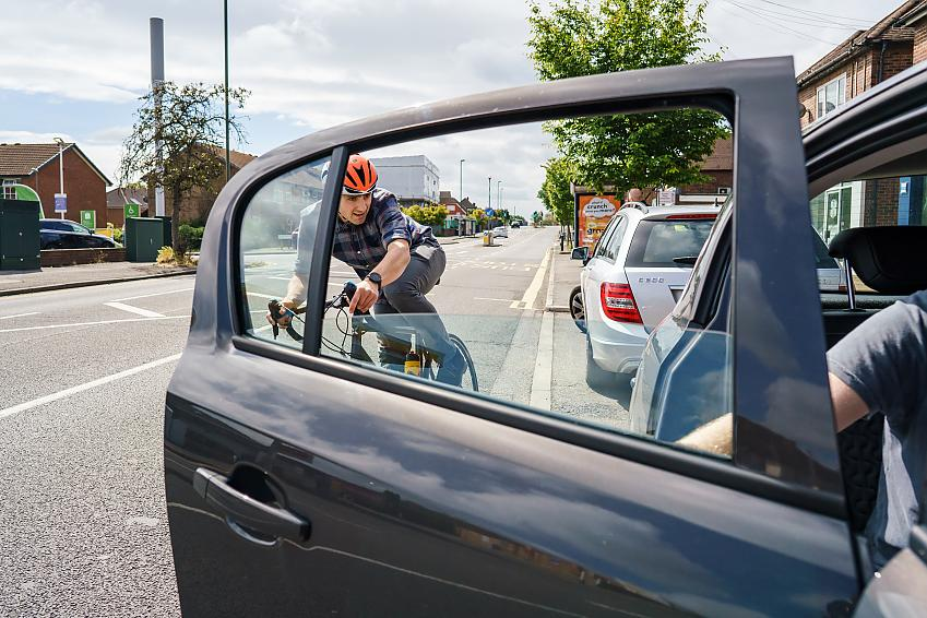 A driver opening their door into the path of a cyclist