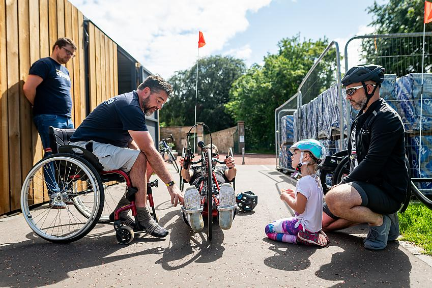 A wheelchair user helps a handcyclist get set up as other cyclists watch on