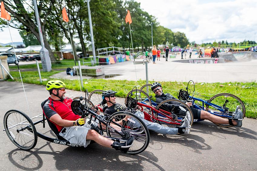 Three handcyclists sharing a joke in the park