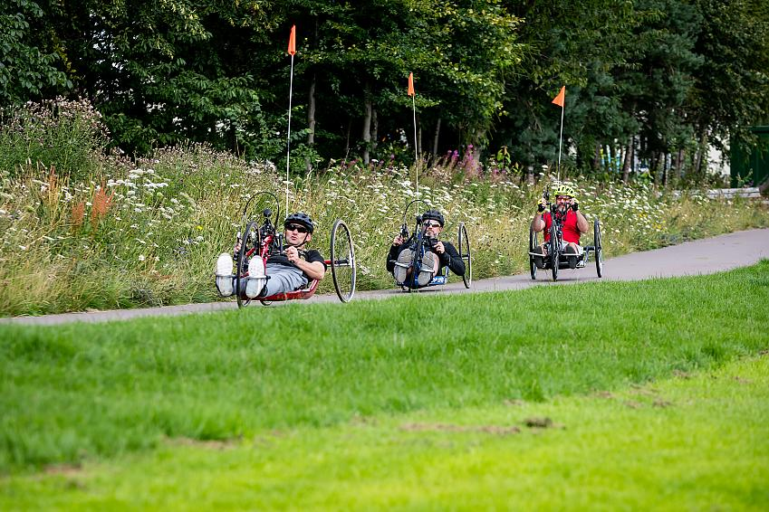 Three handcyclists in the park