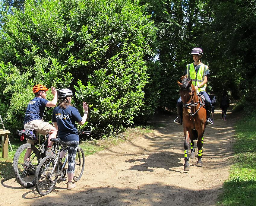 A horse rider smiles and waves at two cyclists who have moved over to the side of the path to let him pass