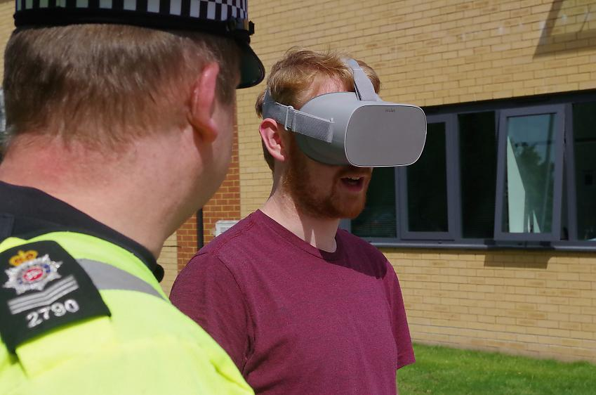 Man wearing virtual reality headset standing next to police officer
