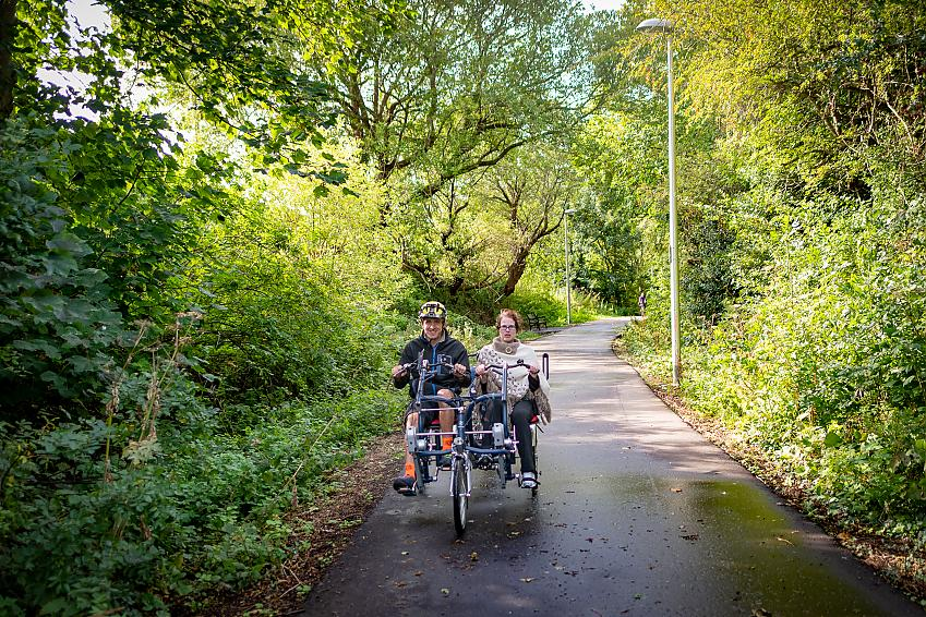 Two people riding an adapted trike along a cycle path through trees