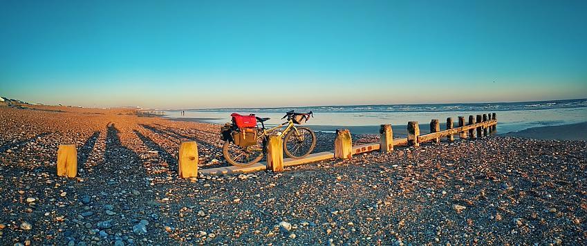 Bike with pannier bags on a misty beach