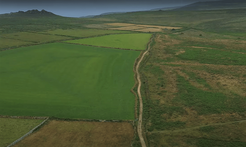 Drone shot of a track running through green countryside