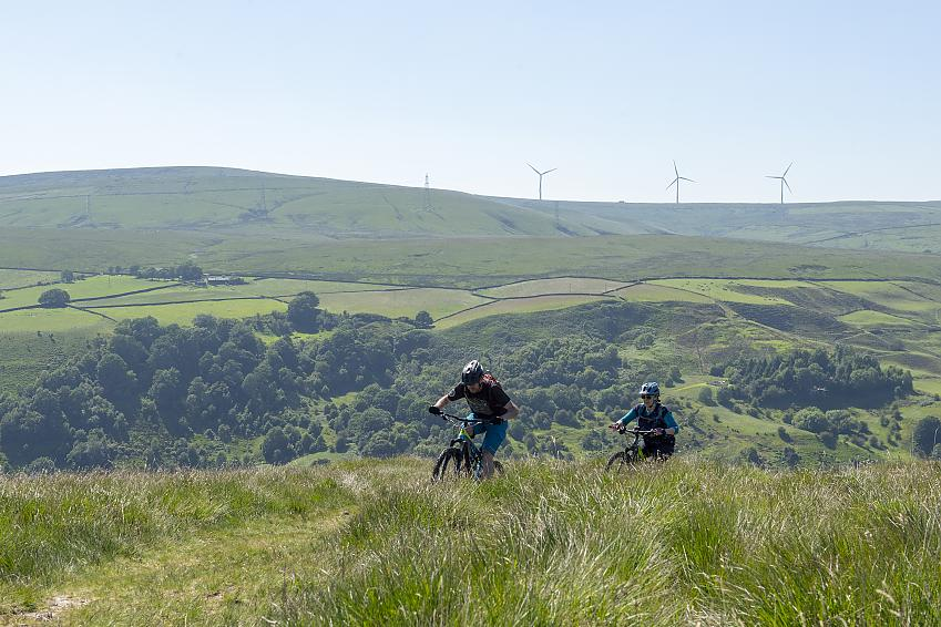 Man and woman mountain biking up grassy hill