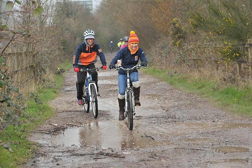 People laugh as they ride through puddles on a muddy track