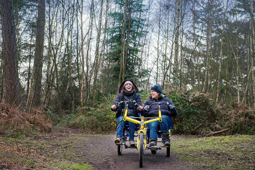 Two women riding together on an adapted tricycle along a woodland trail