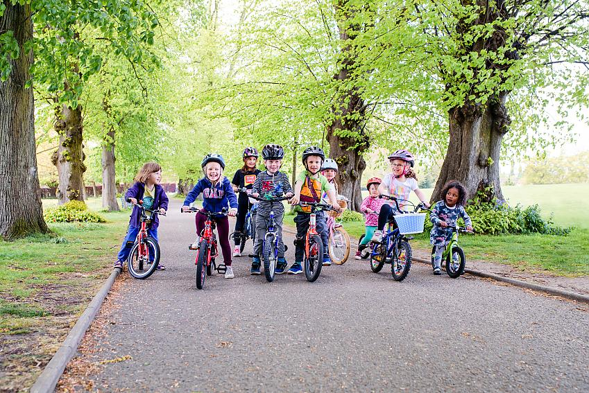 Crowd of children standing astride their bikes laughing