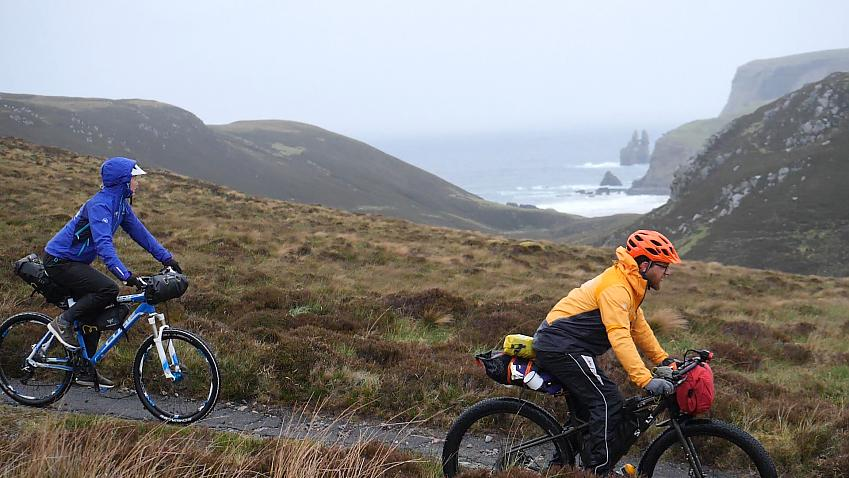 Two mountain bikers riding along a trail by the coast