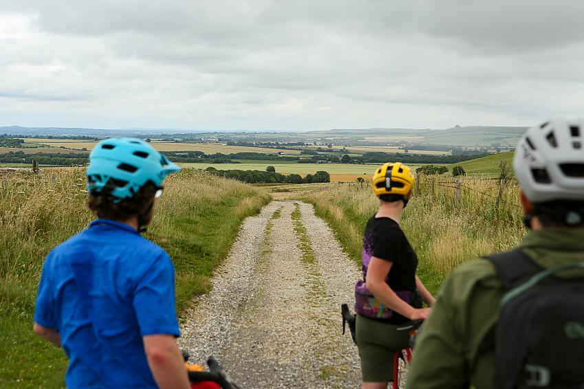 People wearing cycle helmets look down a gravel track that stretches to the hills in the distance