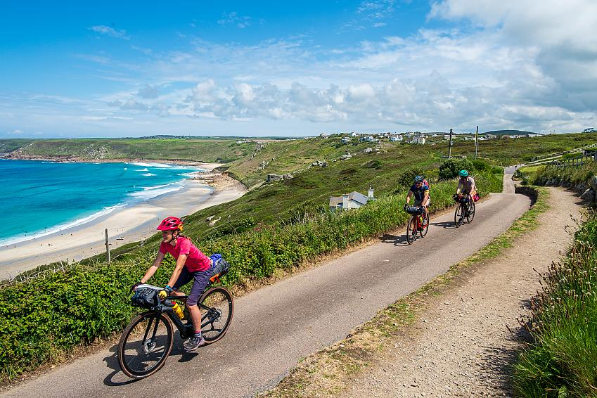Four people cycle along a road with a stunning beach in the background below
