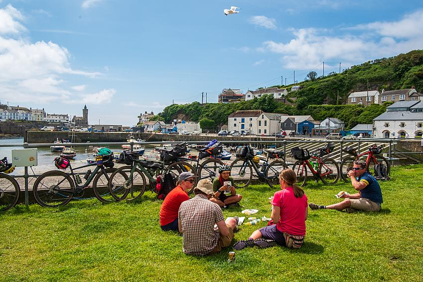 A group of people sit eating pasties beside a harbour with their bikes leant against the railings