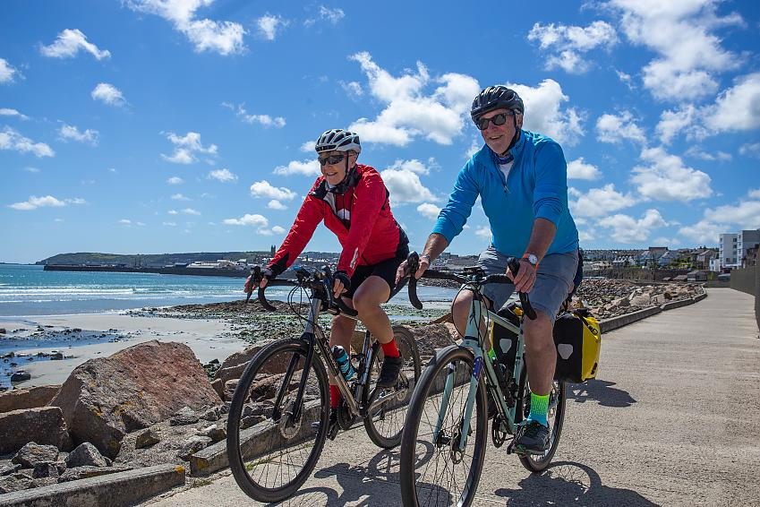 Two people cycle along a cycle path beside the sea