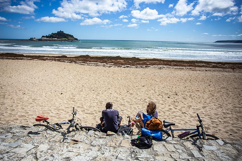 Two people sit on a beach with bikes beside them, looking out at St Michael's Mount