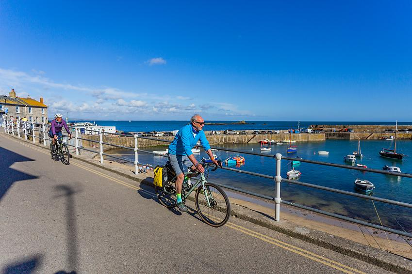 Two people cycle along the side of a harbour