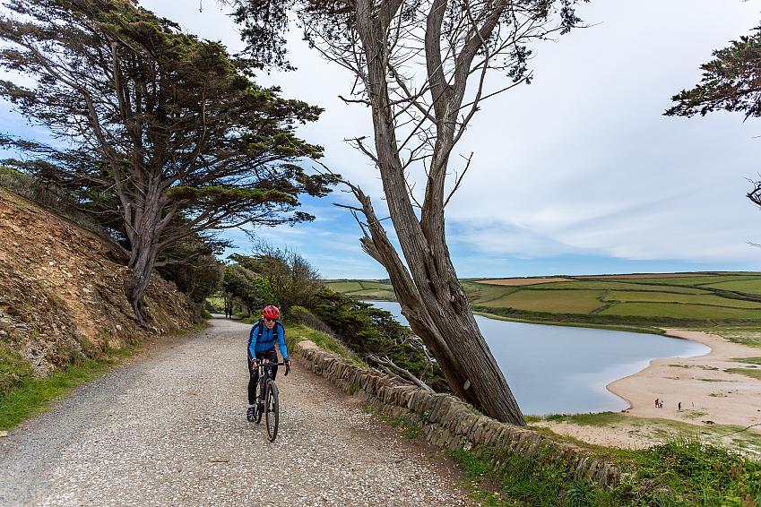 Man rides along a gravel track above a sand bar lake