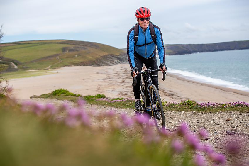 Through pink flowers in the foreground, a man cycles up a hill with a beautiful beach behind