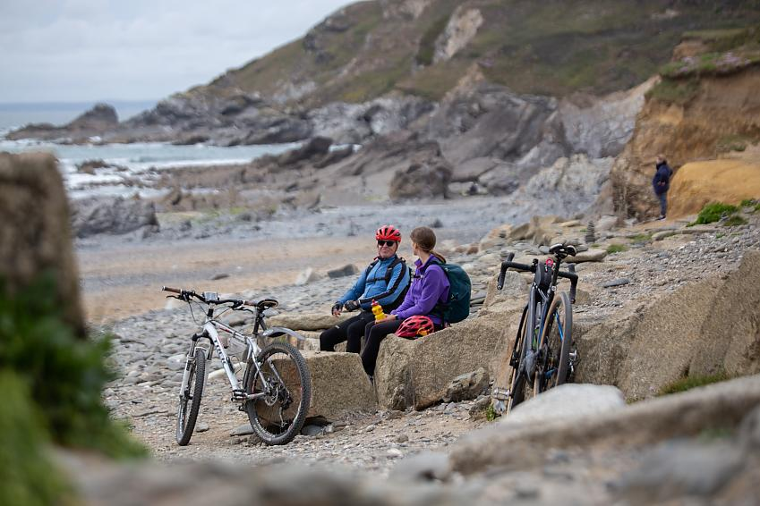 Two people sit in a rocky cove with bikes beside them