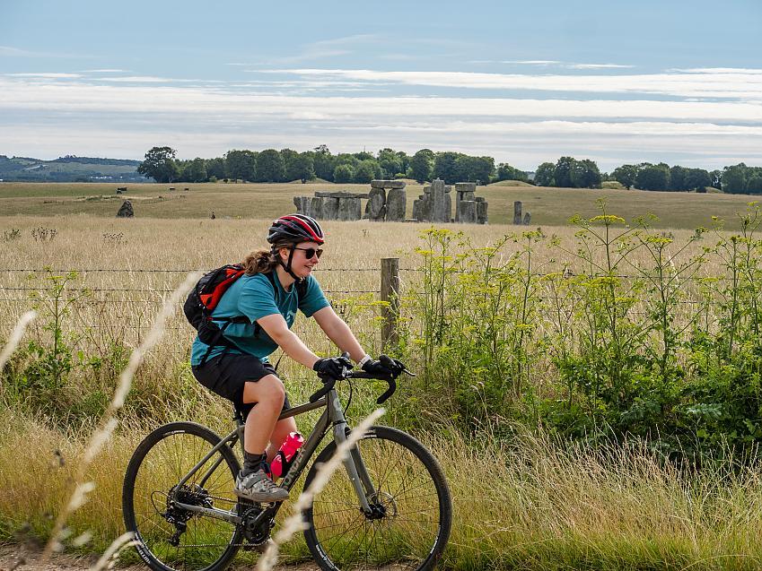 Woman cycling past Stonehenge