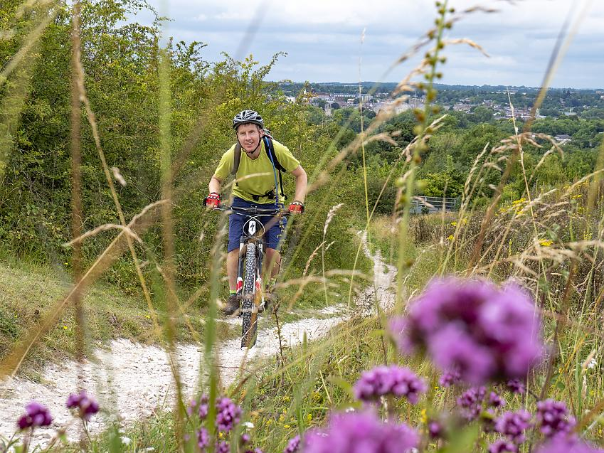 Through a foreground of bright pink flowers, a man on a mountain bike rides up a hill towards the camera