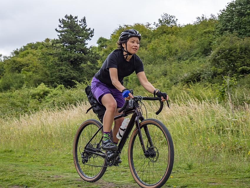Woman riding a bike through an area of grassland and trees
