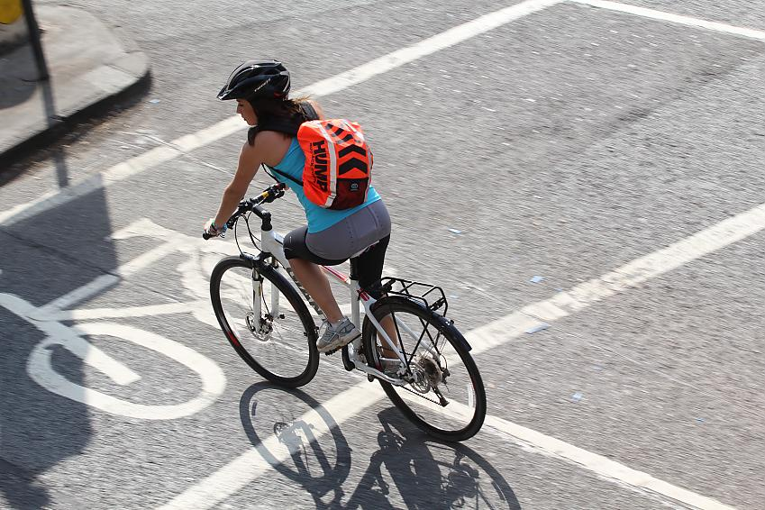 Woman cycling at a city junction