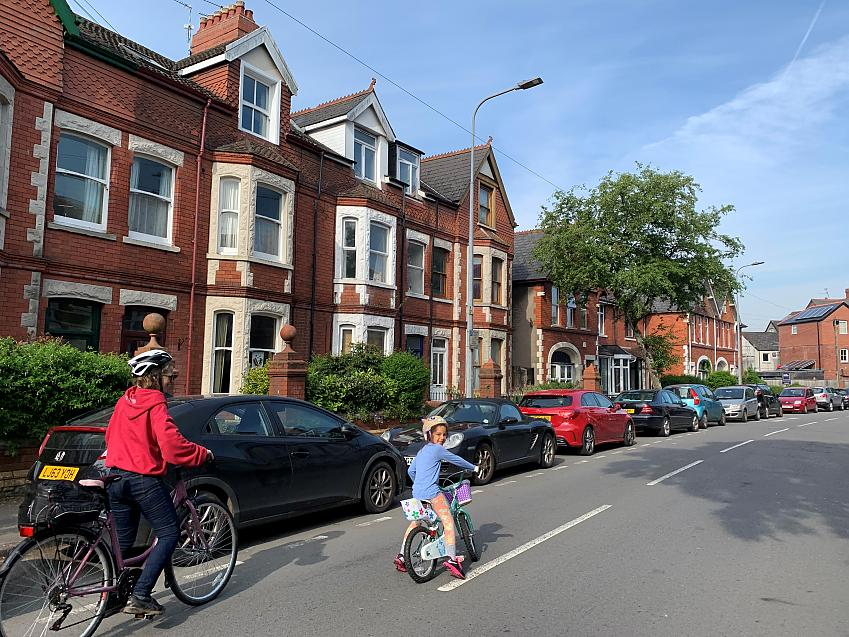 Woman and young child cycling along a quiet residential street