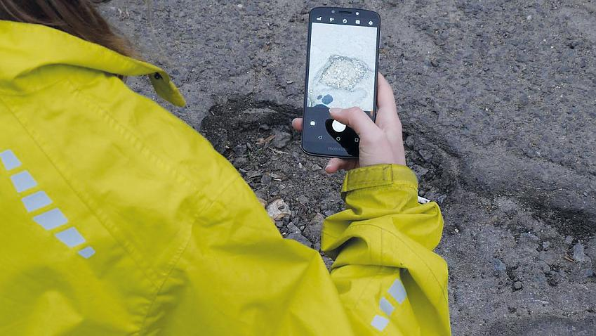 Close-up of person taking a photo of a large pothole with their phone