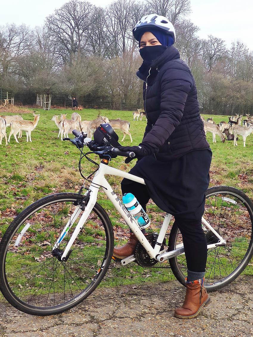 Syeda on her bike in front of a field of deer