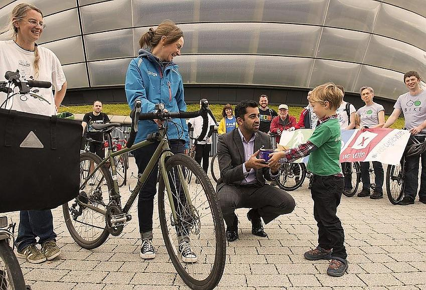 Suzanne (second from left) and her son (right) presenting a cake from WalkCycleVote cycle campaigners to the (then) Minister of Transport