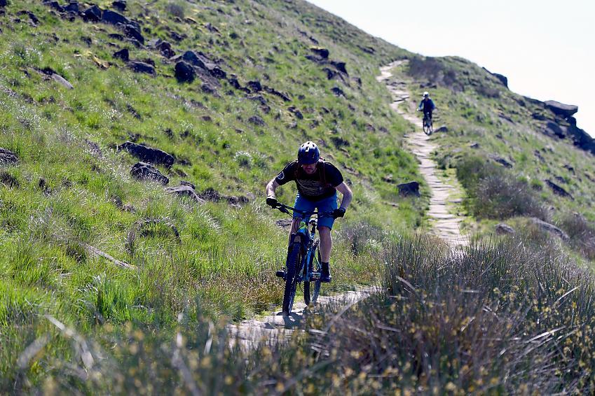 Mountain biker riding down a stone trail