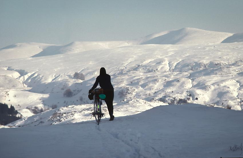 A cyclist standing on a snowy plateau