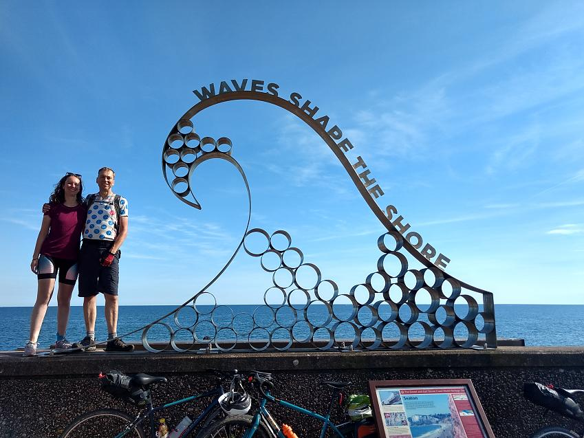 A man stands with his daughter in front of a sculpture of a wave by the coast