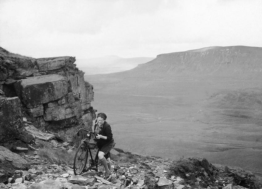 B+W photo of a woman pushes her bike up rough terrain