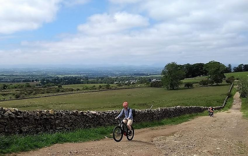 Man riding an e-mountain bike up a hill