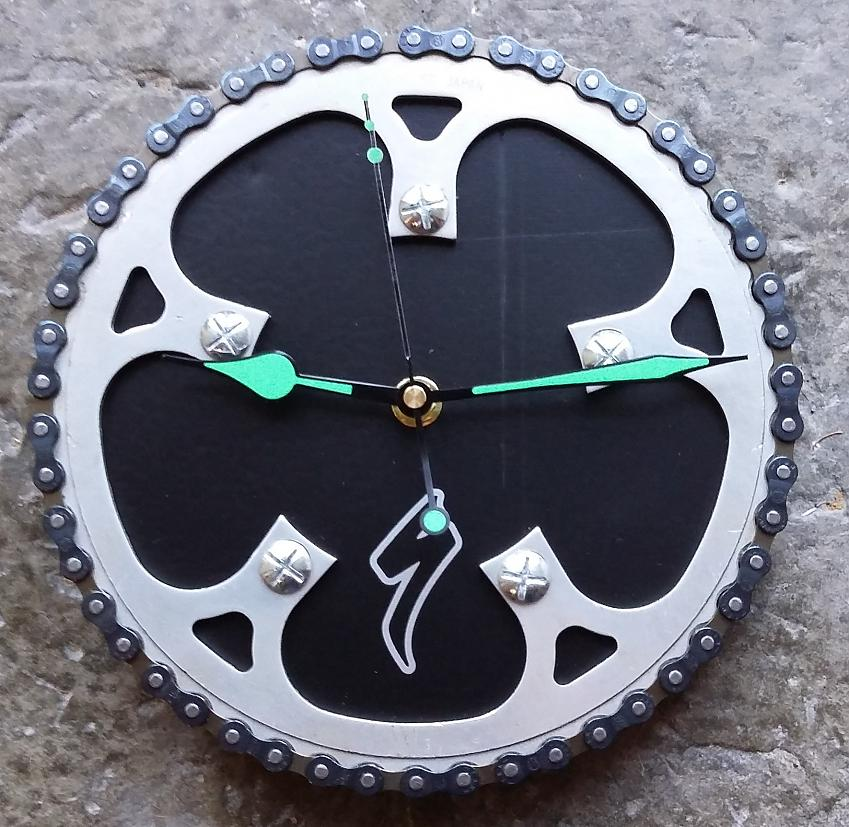 A clock made from bicycle parts with green hands