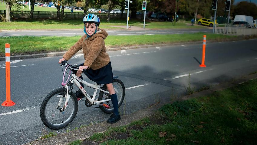 Young girl smiling on a bike cycling along a temporary cycle lane marked with cones